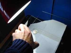 """Figura 2.2: il vetro va interposto tra moneta e l'obiettivo fotografico (la fotocamera deve essere già attaccata sullo stativo). Ruotare l'inclinazione del vetro per """"cercare"""" l'angolo di inclinazione più adatto."""