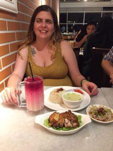 Laura sentada a la mesa con una bebida rosa y tres platos delante, pollo, arroz y noodles y tazitas de salsa