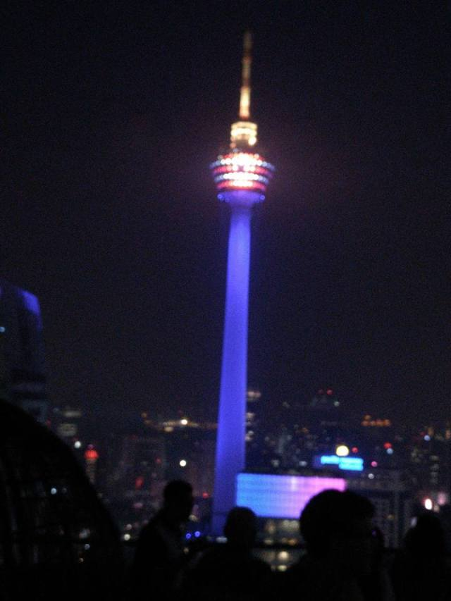 Torre de comunicaciones iluminada en azul sobre la noche de Kuala Lumpur