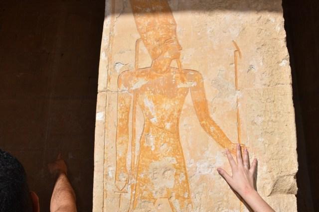 La mano de Laura tocando un dibujo egipcio en el templo de Hatshepsut