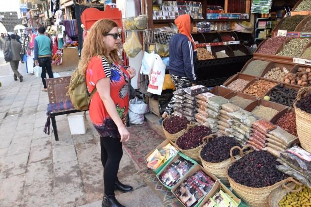 Laura delante de un puesto con muchas especias diferentes llenas de colores