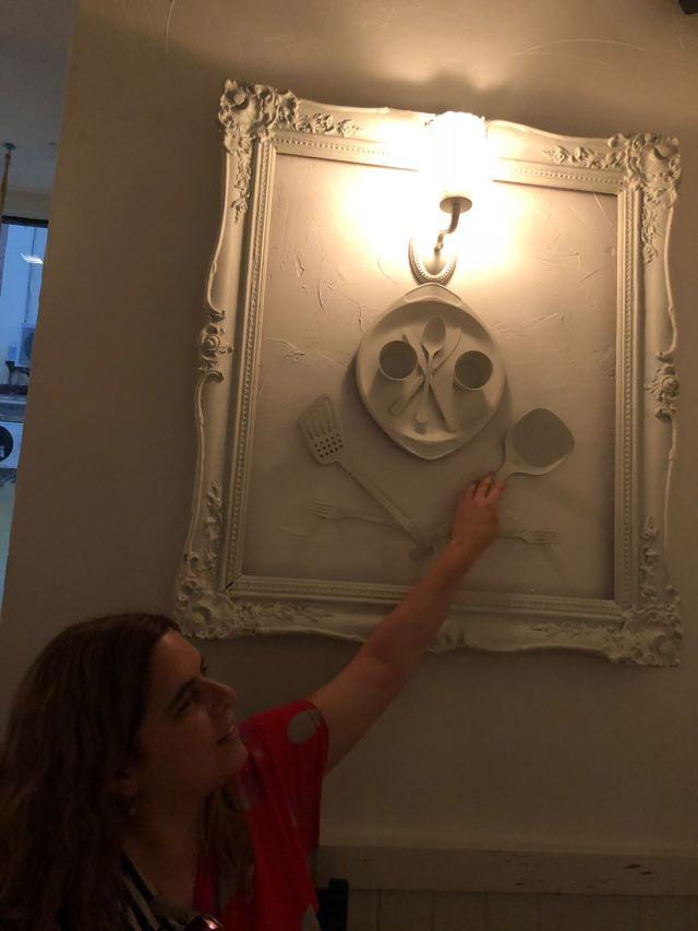 Laura tocando un cuadro en relieve. El cuadro tiene una cuchara, espátula, boles y algunos cubiertos pegados