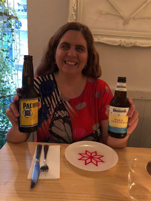 Laura sujetando la sdos cervezas, una en cada mano