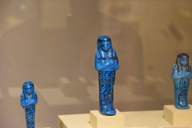 Tres figuras turquesas. Representan a egipcios con los brazos cruzados y las piernas juntas. Tienen inscripciones egipcias en negro abajo