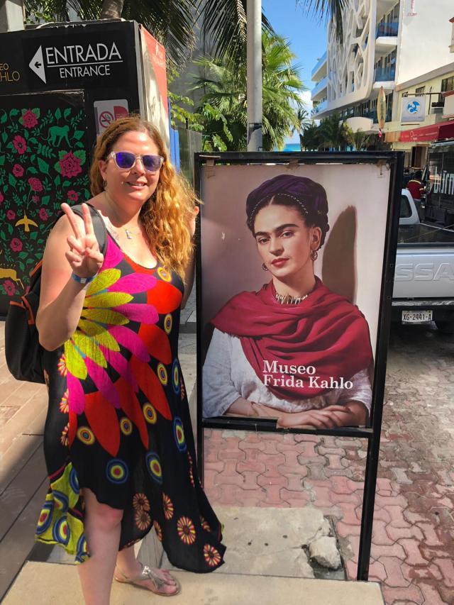 Laura al lado del retrato de Frida Kahlo en un cartel a la entrada del museo en playa del Carmen