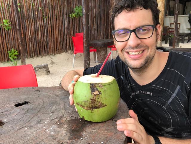 David bebiendo de un coco en Playa Paraíso