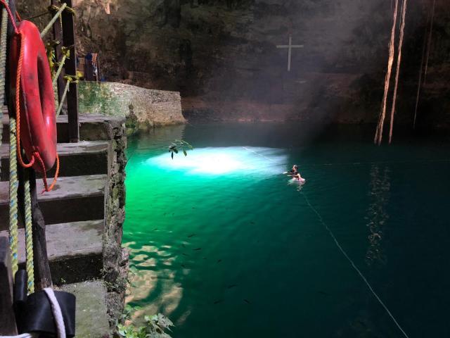 e ve la cueva con un tragaluz en el centro que proyecta un circulo de luz en medio del cenote, escaleras de  piedras y algunas personas bañandose