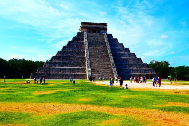 Pirámide de Chichén Itzá con un suelo de césped bajito, y un despejado cielo azul. La pirámide sube de forma escalonada tiene una escalera central y arriba del todo tiene una base muy amplia