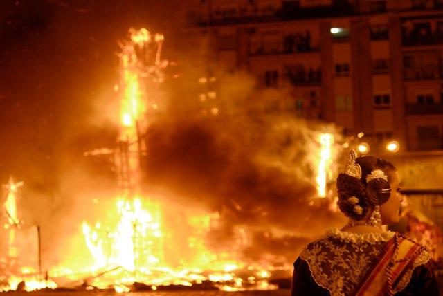 En la image predominan los tonos naranjas de fuego. Al fondo un bloque de edificios, de noche, un ninot arde e ilumina toda la fotografía