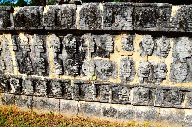 se ve el muro de piedra con muchas calaveras en relieve esculpidas