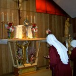 Rev. Mother and the Handmaid making final vows place lighted oil lamps on the high altar.