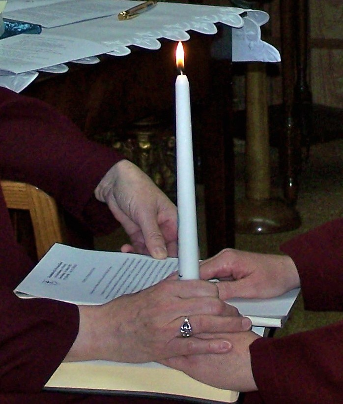 Holding the baptismal candle and pronouncing vows with hands on the Gospel.
