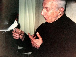 1992, Father Hardon enjoys one of our pet birds, Sereno.