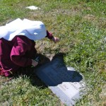 A Handmaid tends to our founder's grave.