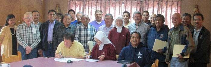 Members of the Jemez Pueblo Tribal Council of tribal leaders pose for a photo as Mother Marietta and Governor Madalena sign the papers.