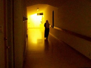 A Handmaid walks up the cloister to her nocturnal holy hour.