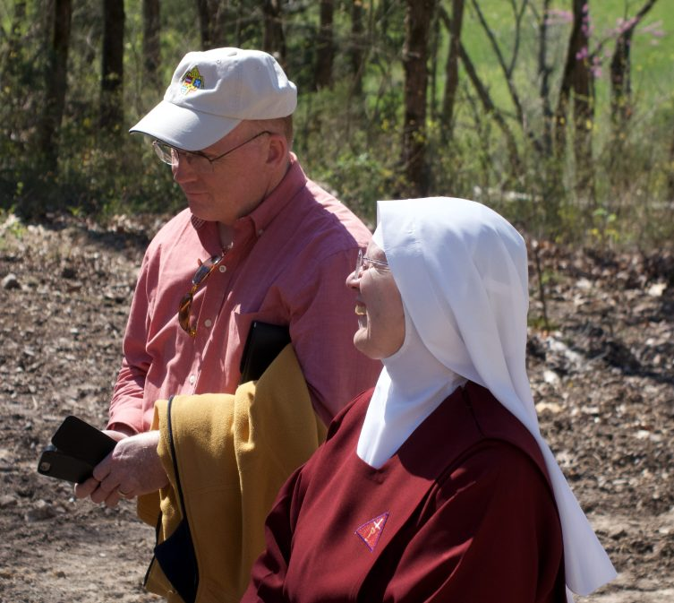 Paul Simoneau, Vice-Chancellor for Administration, shares a moment with a Handmaid observing the interment.