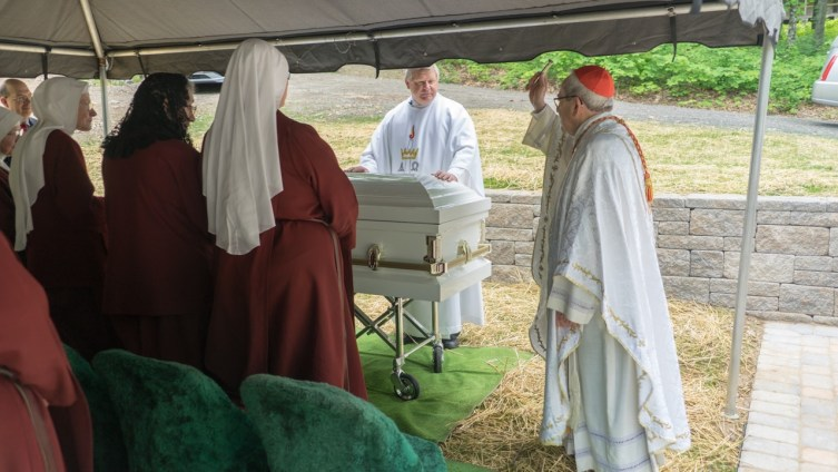 A first for any Handmaid. A prince of the Church, Cardinal Rigali, blesses Sister Mel Pierre at the cemetery.