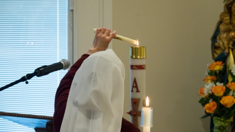Sister Rose Anne lights her baptismal candle from the Paschal candle
