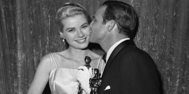 1955. Grace Kelly con l'Oscar si fa baciare da Marlon Brando, pure lui premiato per 'Fronre del porto'.