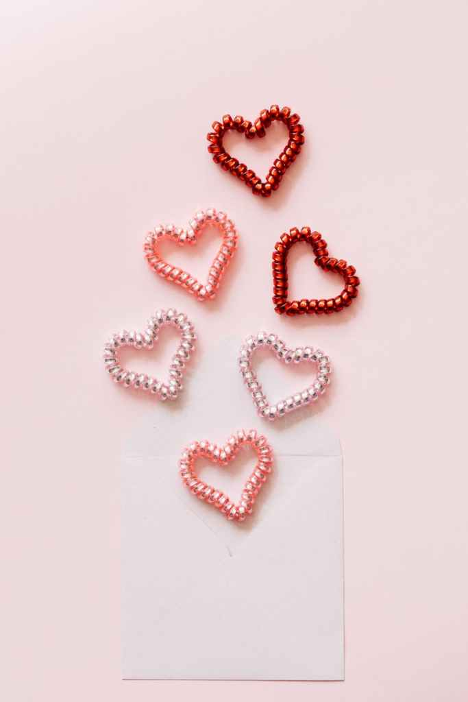 composition of decorative coil hearts and open envelope