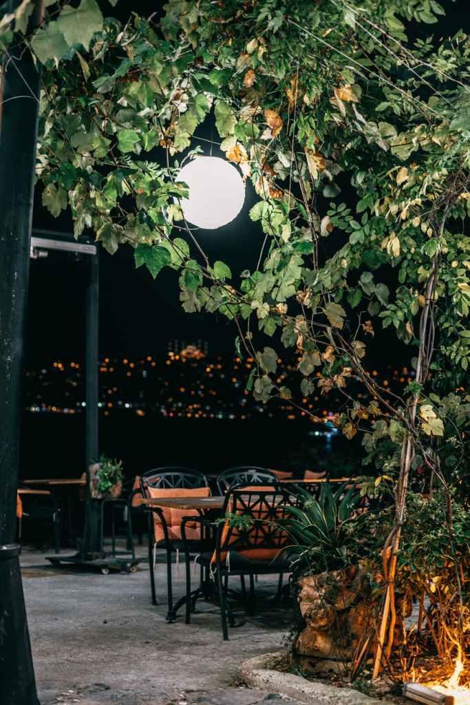 street cafe among green trees under bright illumination of lamp