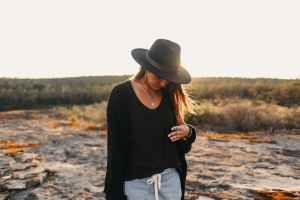 anonymous woman in hat on stony terrain