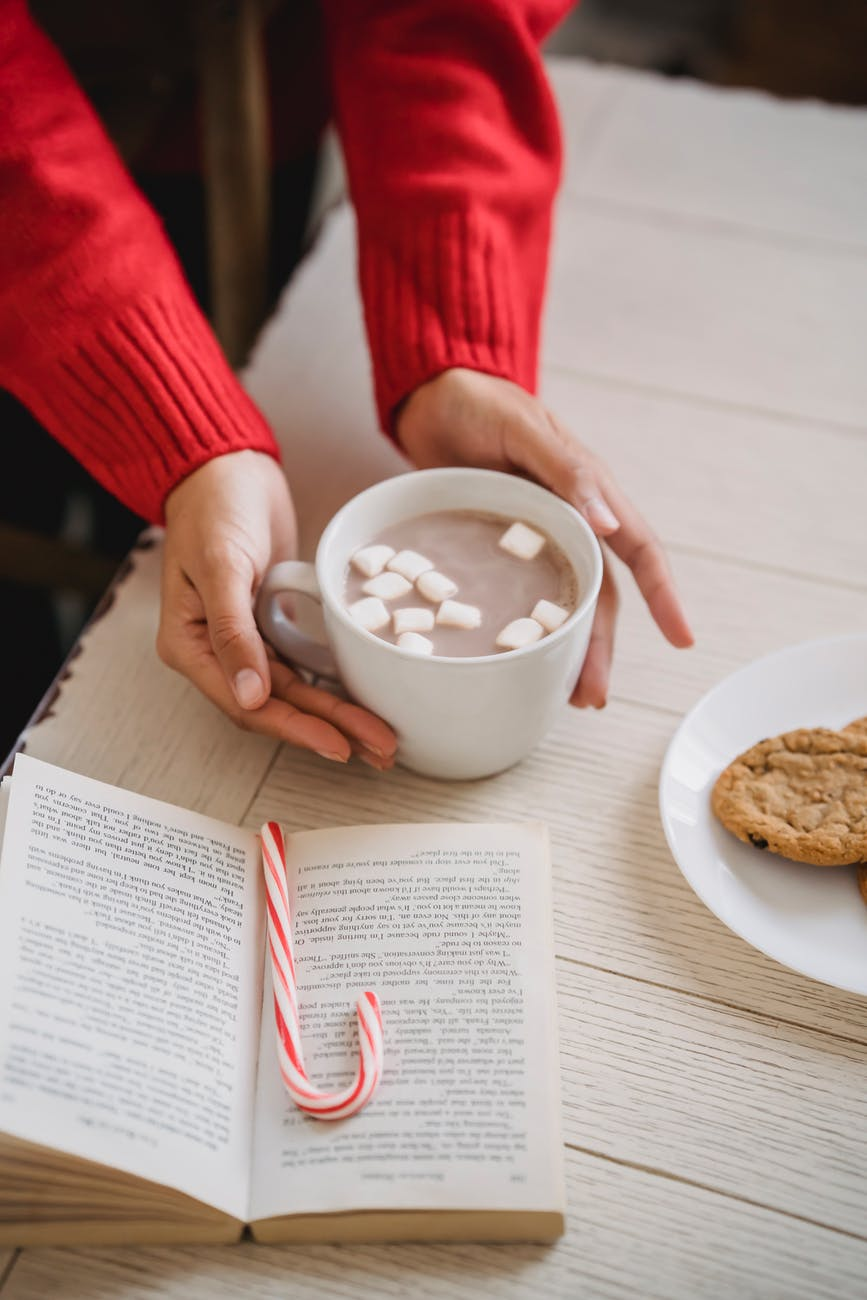 crop woman with cocoa and book
