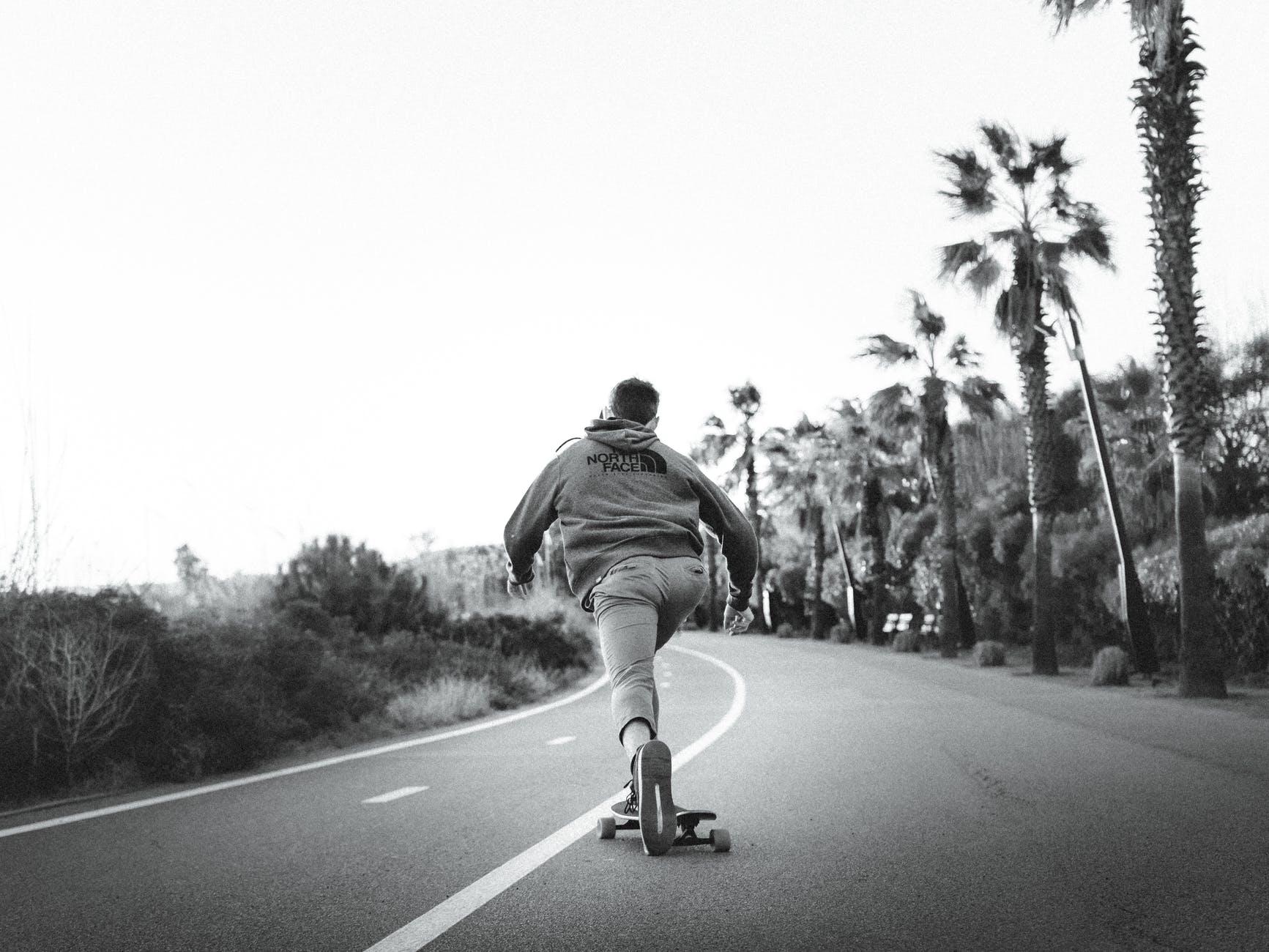 unrecognizable man skateboarding on asphalt road