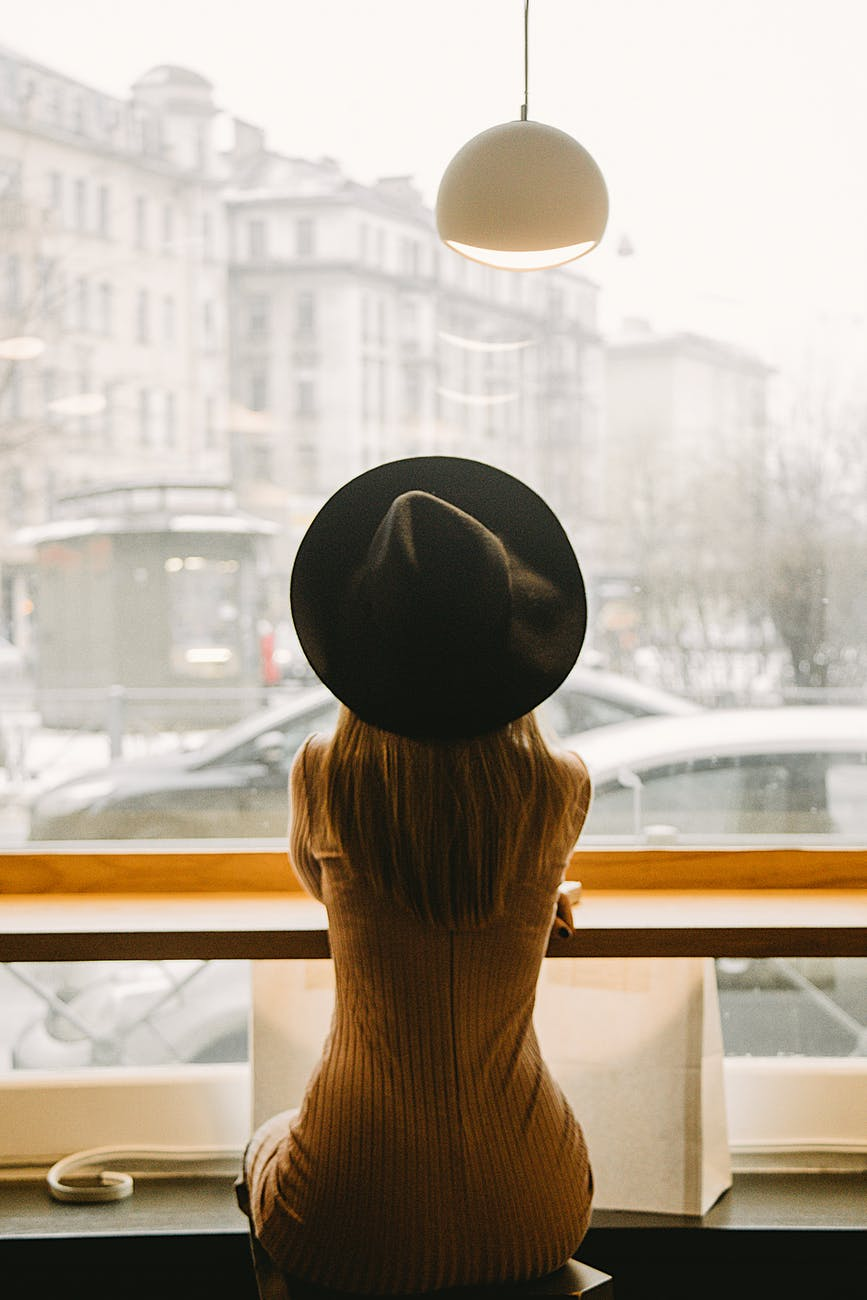 woman in black hat sitting in front of glass window