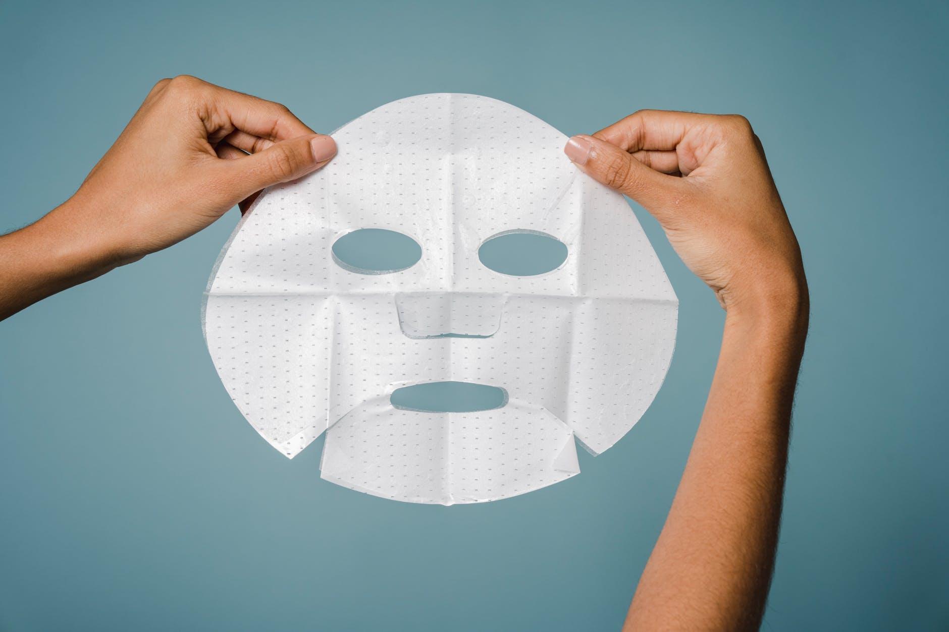 female showing sheet mask against blue background