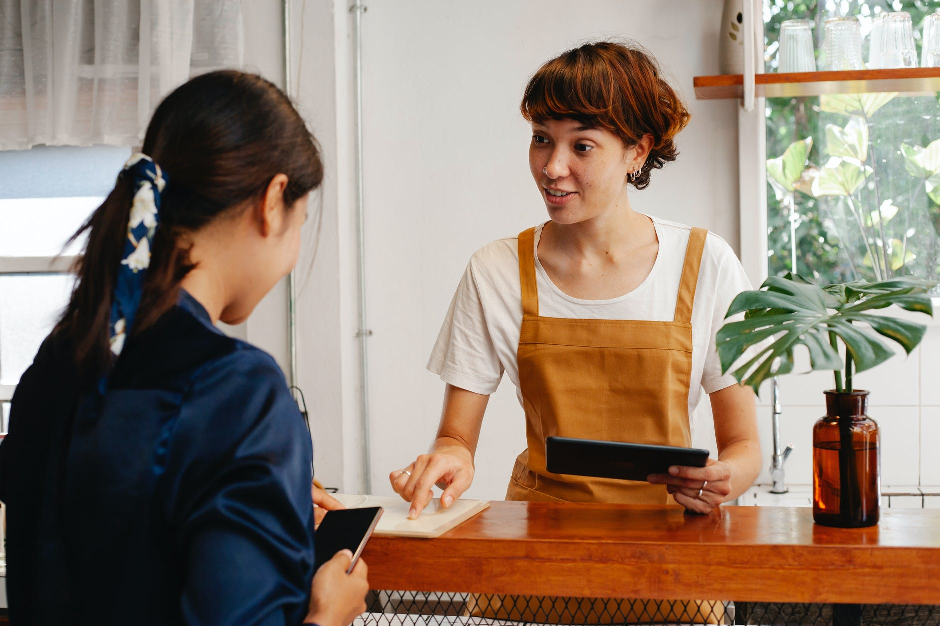 smiling employee with tablet talking to colleague in cafe