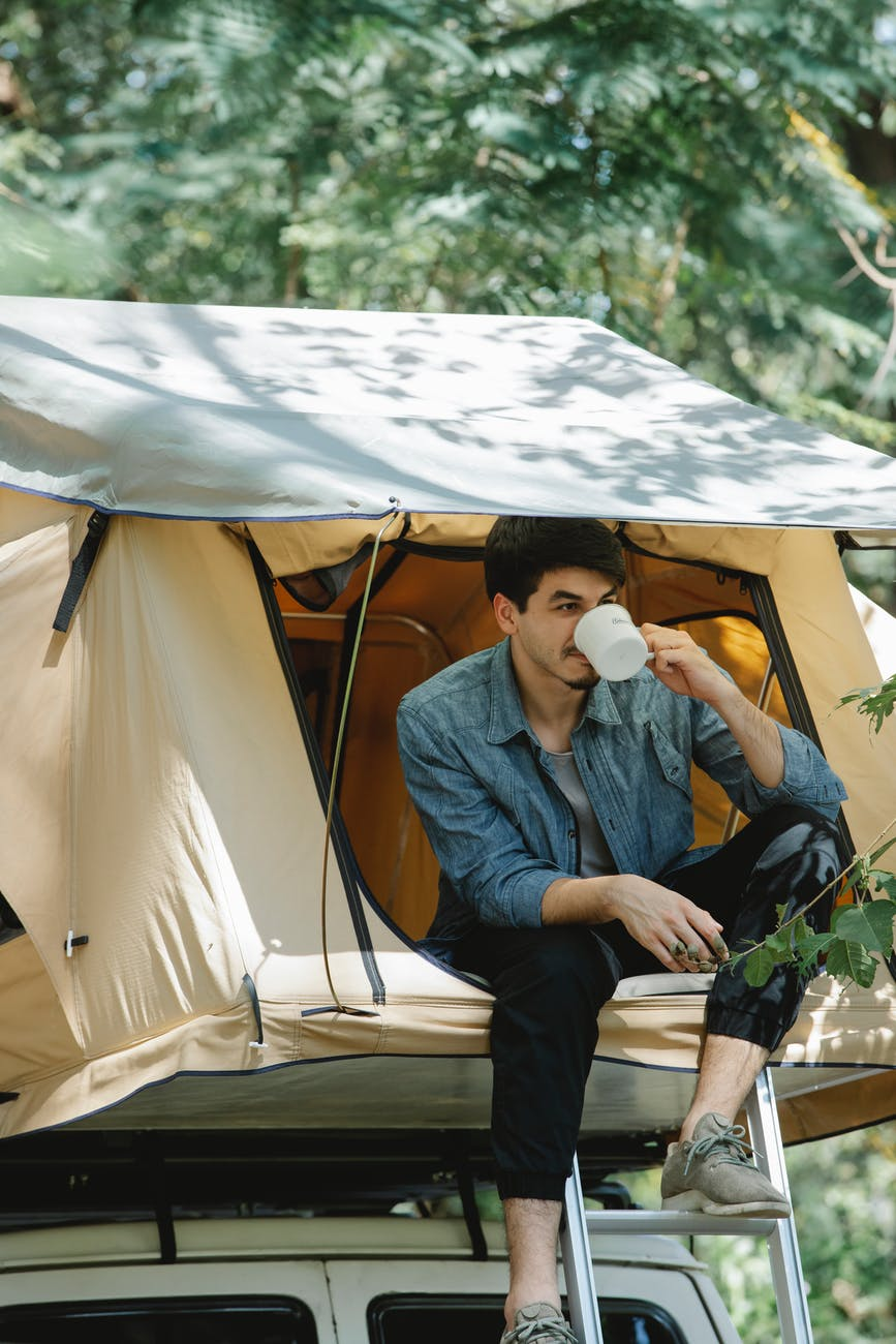 young man drinking coffee in tent during camping in forest