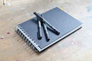 notepad spiral with pencils and sketchbook on table
