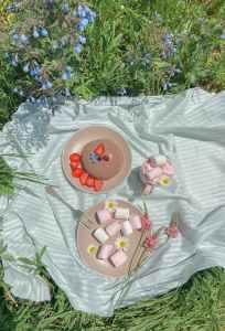 delicious sweet marshmallows near plate with cake decorated with berries