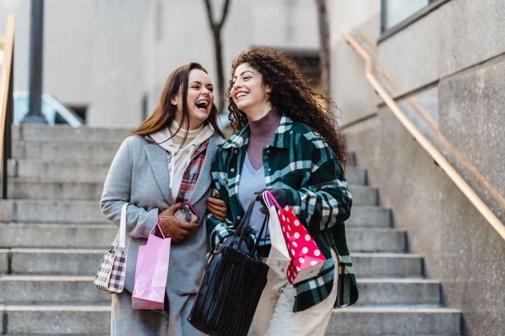 excited young diverse ladies laughing while walking downstairs in city after shopping