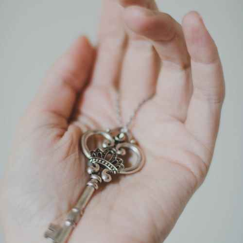 person holding silver colored skeleton key