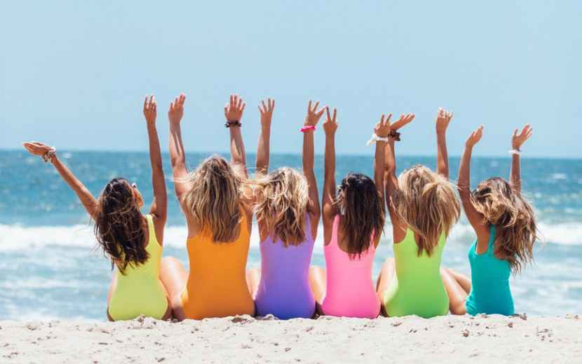 back view photo of six girls wearing swimsuit sitting on white sand