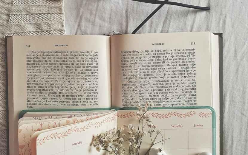 black framed eyeglasses next to book