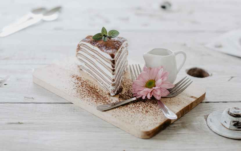 delicious piece of cake and flower on wooden table