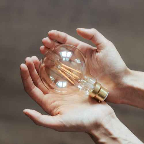 unrecognizable woman demonstrating light bulb in hands