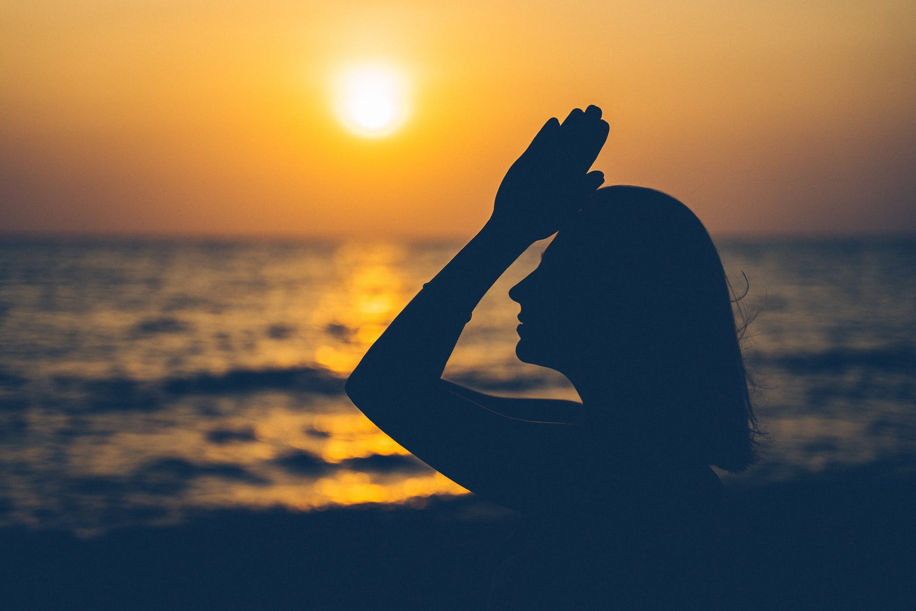 silhouette of woman standing against sunset