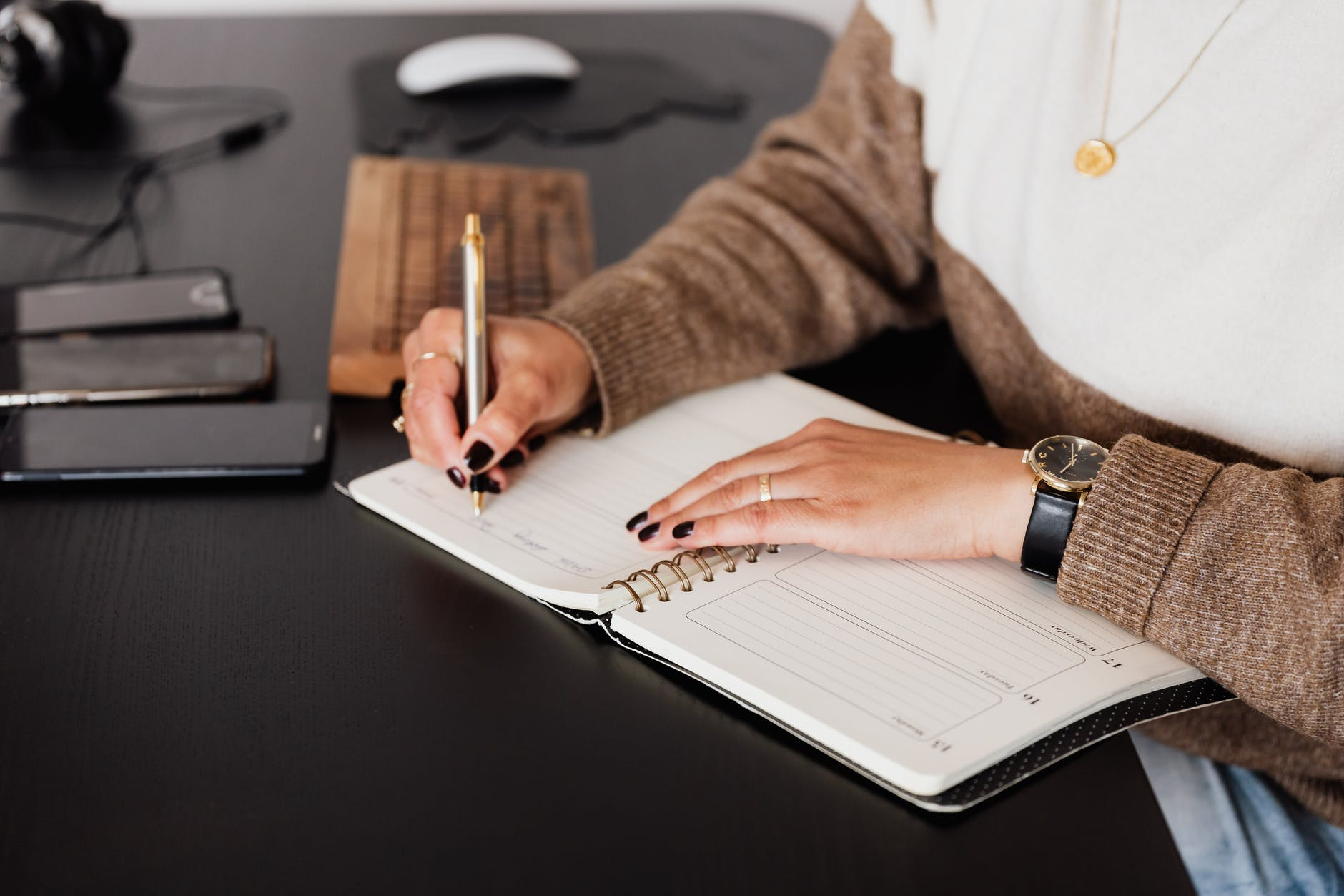 crop stylish woman taking notes in notebook