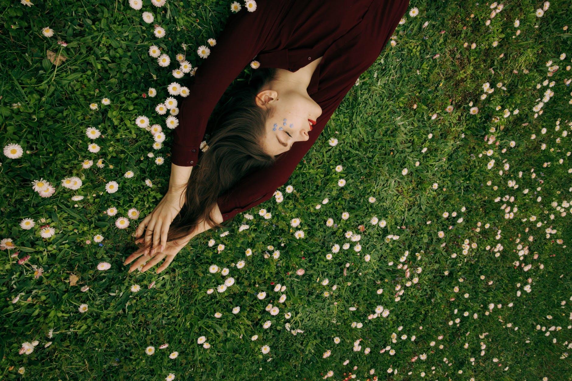 woman in maroon long sleeve shirt lying on white flower field