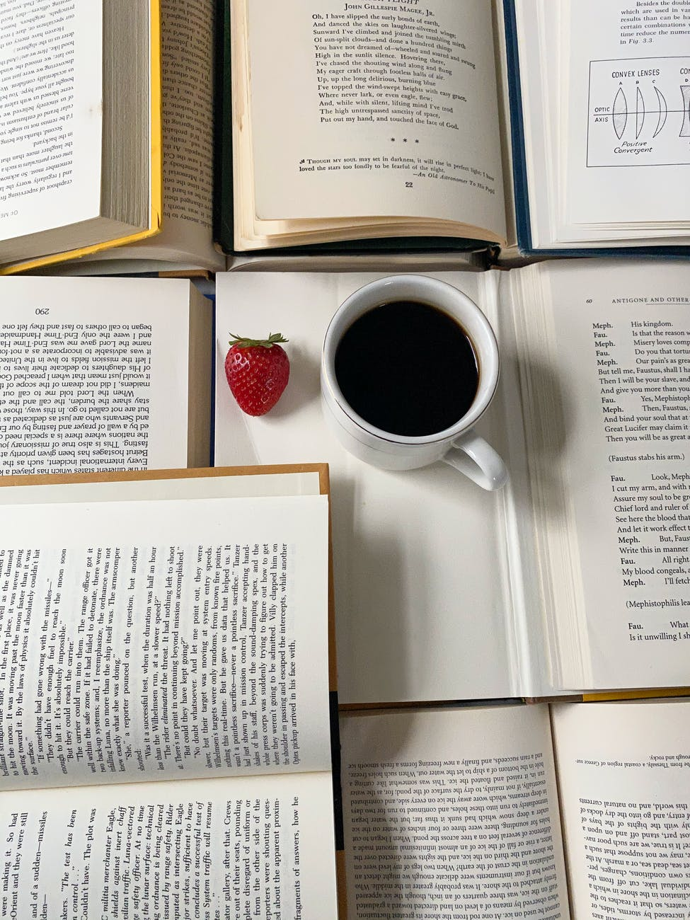 mug with coffee and strawberry on opened books