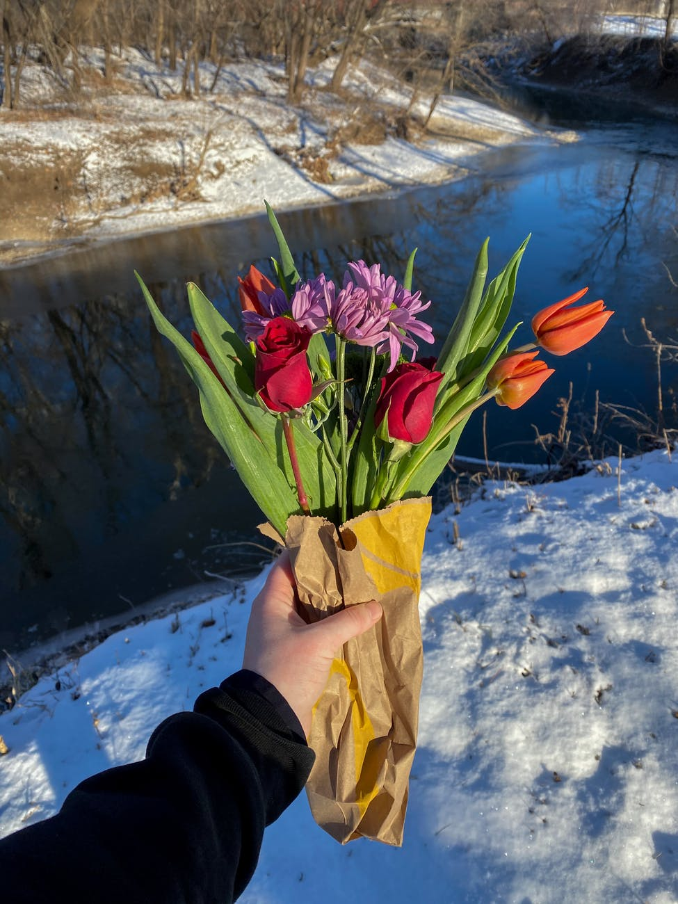 faceless person holding bouquet of fresh flowers on snowy river shore