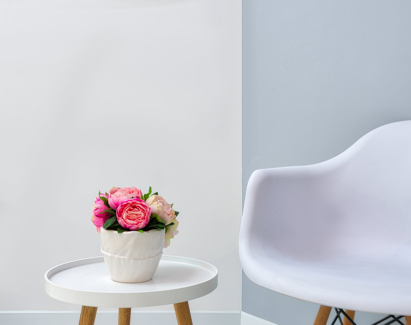 chair near table with vase of flowers