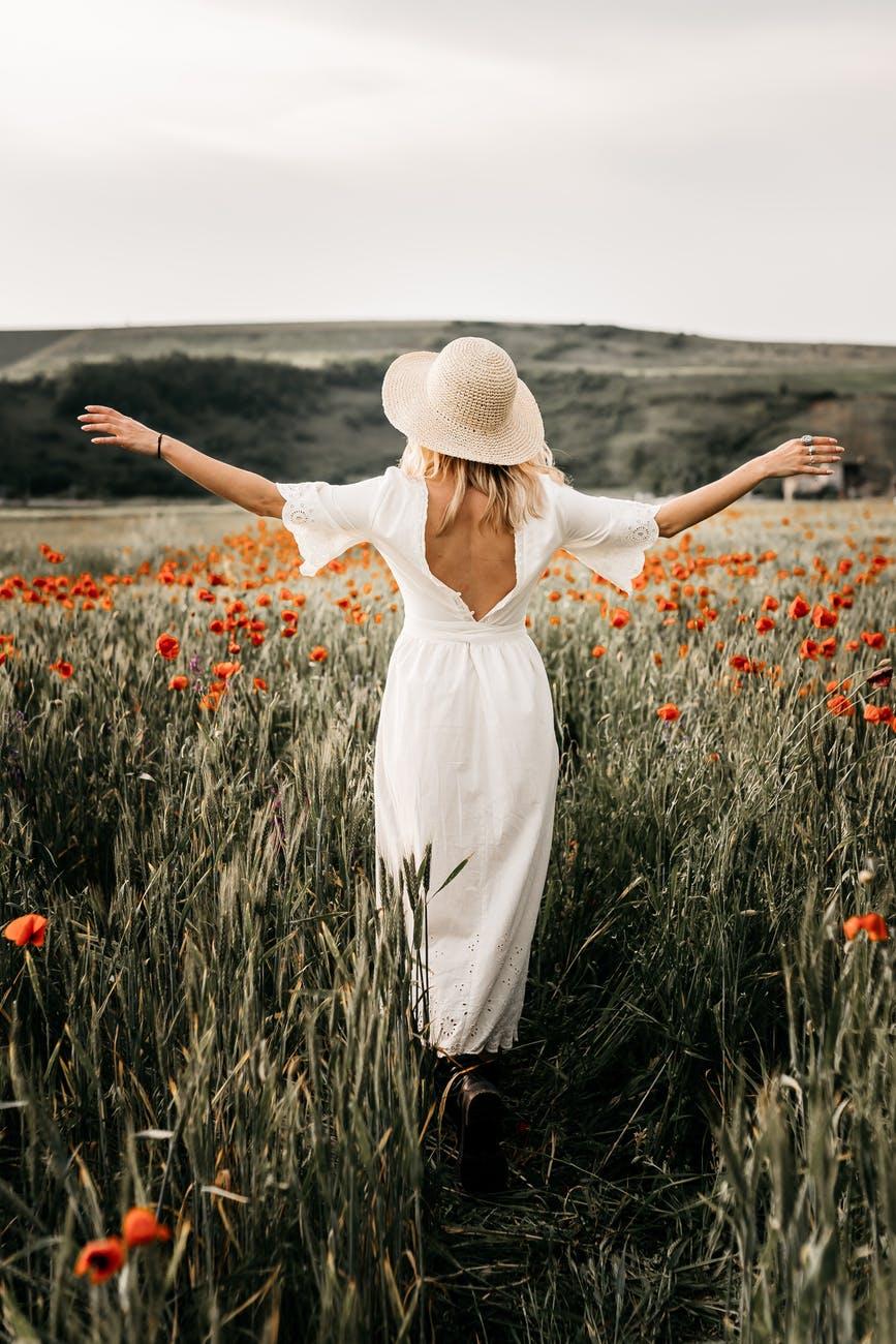 elegant woman in hat walking in field with flowers