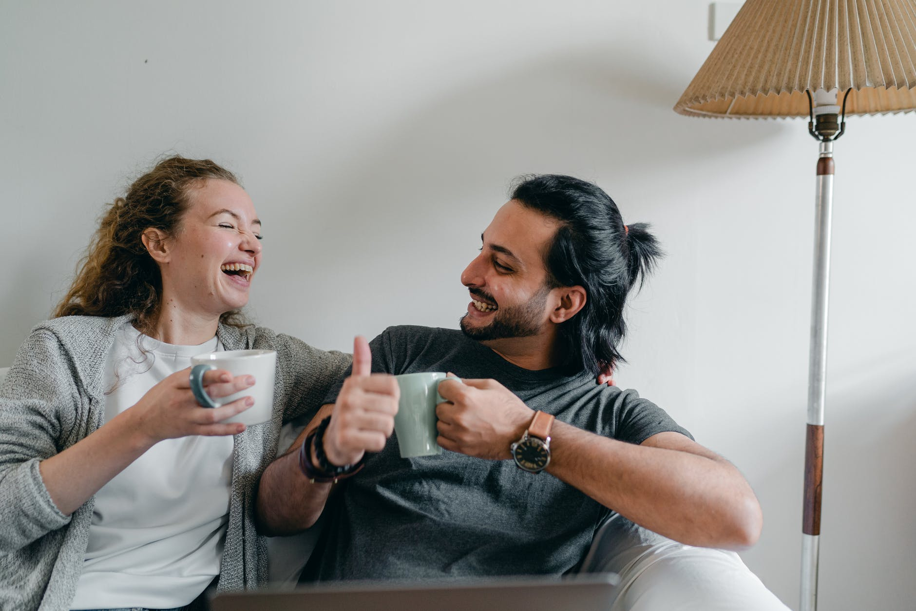 happy multiethnic couple drinking coffee and showing like gesture