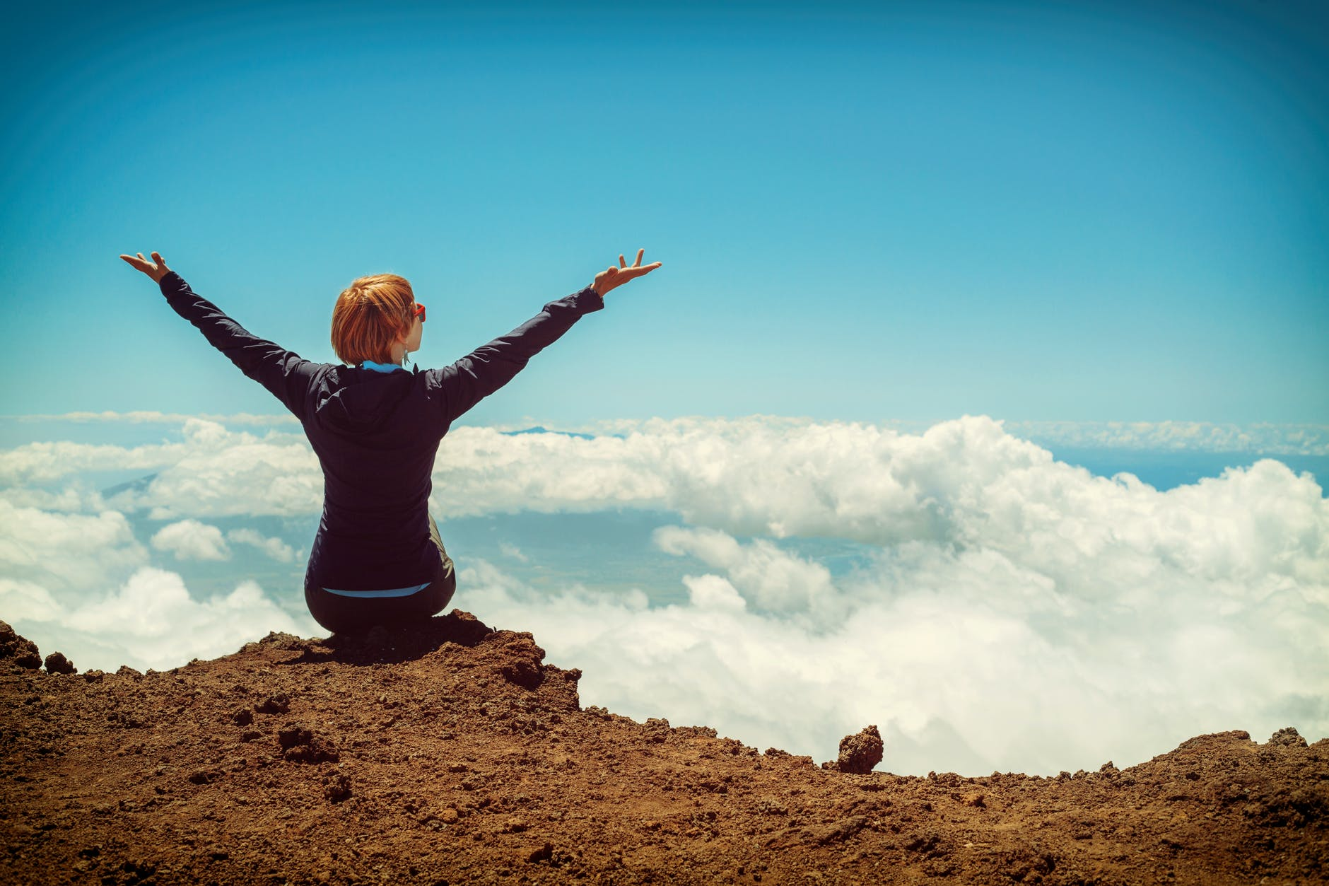 person sitting on cliff raising up both hands